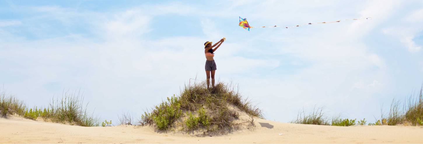 woman flying a kite on the beach in the OBX area
